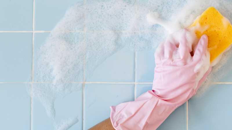 Persona fregar los azulejos de la cocina con una esponja